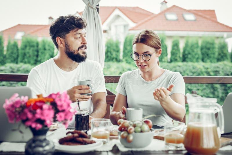Attraktiver Gatte, der Kaffeetasse hält und auf seine Frau hört lizenzfreies stockfoto