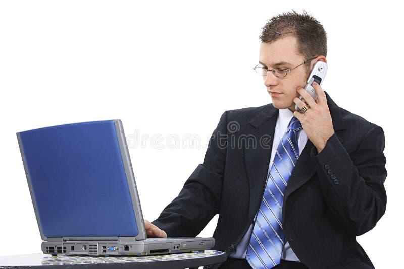 Attraktiver Geschäftsmann in der Klage mit Computer und Mobiltelefon stockfotos