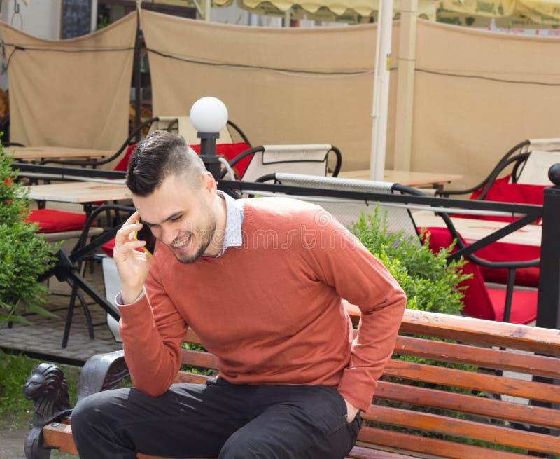 Attraktiver Geschäftsmann in einer rosa Strickjacke mit dem Telefon lizenzfreies stockbild