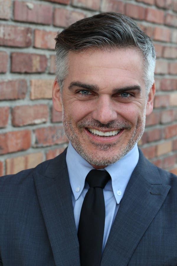 Attraktiver Geschäftsmann mit einem sehr zynischen Lächeln lizenzfreies stockfoto