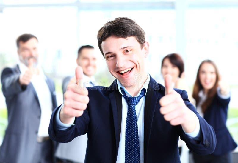 Attraktiver Geschäftsmann mit Team im Büro, das sich Daumen zeigt lizenzfreie stockfotos