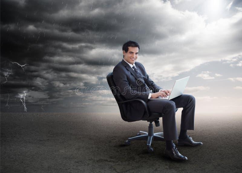 Attraktiver Geschäftsmann unter Verwendung seines Laptops draußen während stürmischen wir stockbild