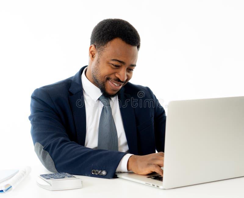 Attraktiver glücklicher hübscher Afroamerikanergeschäftsmann, der an Laptop-Computer auf Schreibtisch im Büro arbeitet stockfotos