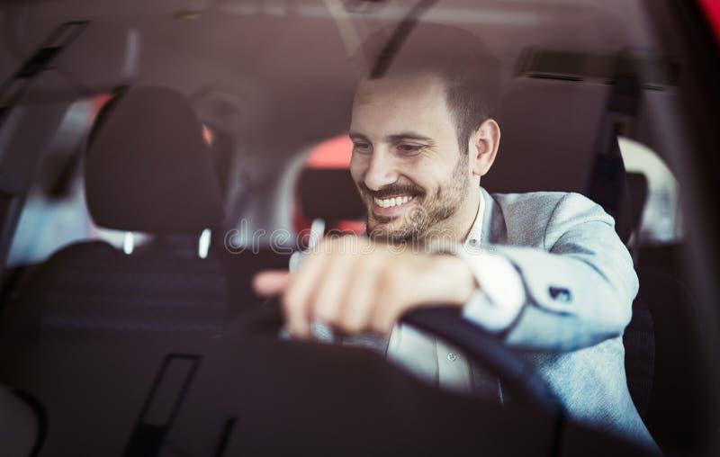 Attraktiver glücklicher junger Mann, der Auto und das Lächeln fährt lizenzfreie stockfotos