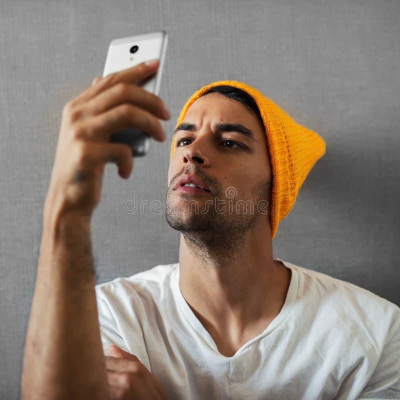 Attraktiver, hübscher und ernster junger Mann, etwas lesend und nehmen selfie Tragender orange Hut und graues scraf auf grauer Wa lizenzfreie stockfotografie