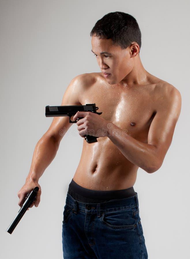Attraktiver hemdloser Mann mit Gewehren stockbild