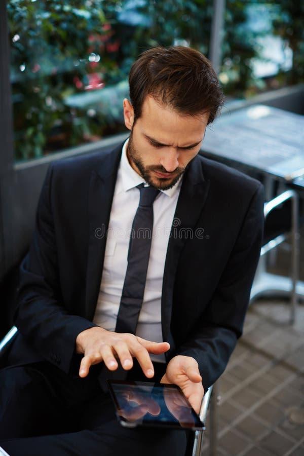 Attraktiver intelligenter Manngebrauchs-Tabletten-PC, der im Internet grast lizenzfreies stockfoto