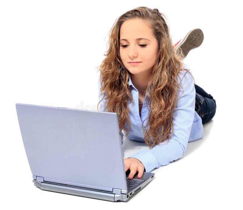 Attraktiver Jugendlicher, der Laptop verwendet stockfoto