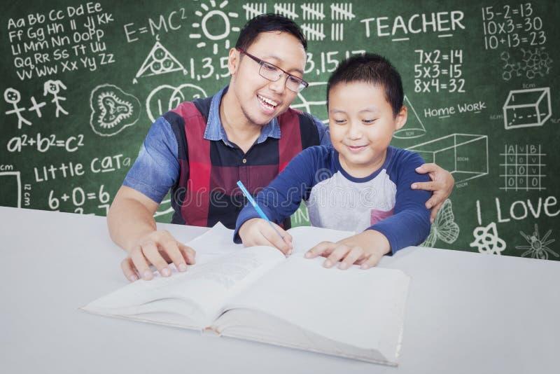 Attraktiver Junge, der in der Klasse mit Tutor studiert stockbild