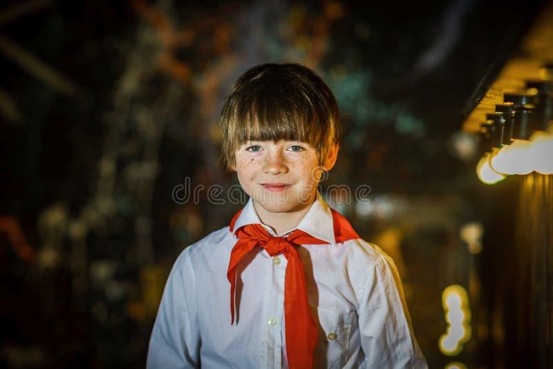 Attraktiver Junge der Rothaarigen kleidete wie sowjetischer Pionier mit roter Bindung an stockfoto