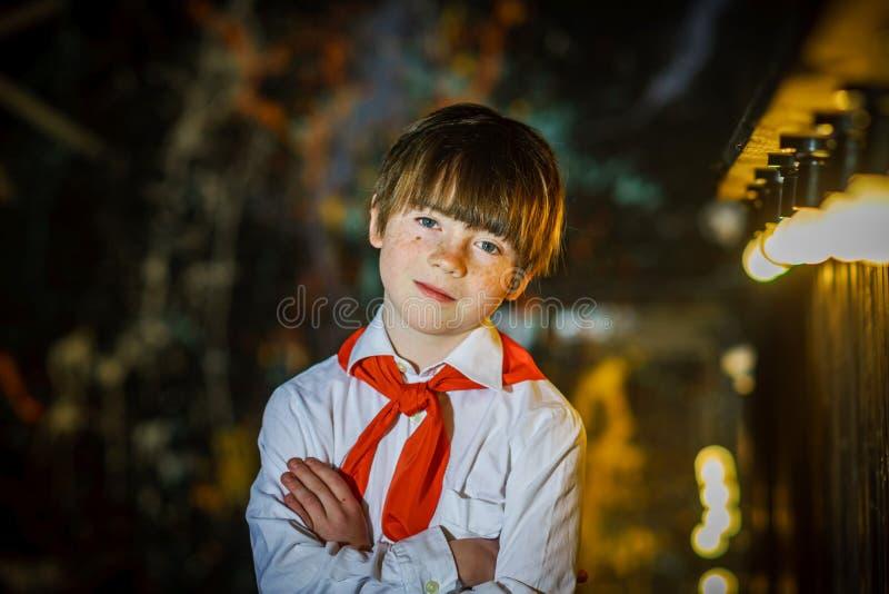 Attraktiver Junge der Rothaarigen kleidete wie sowjetischer Pionier mit roter Bindung an stockfotos