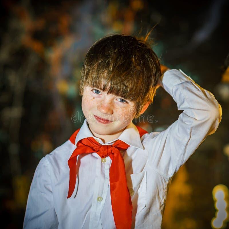 Attraktiver Junge der Rothaarigen kleidete wie sowjetischer Pionier mit roter Bindung an stockfotografie
