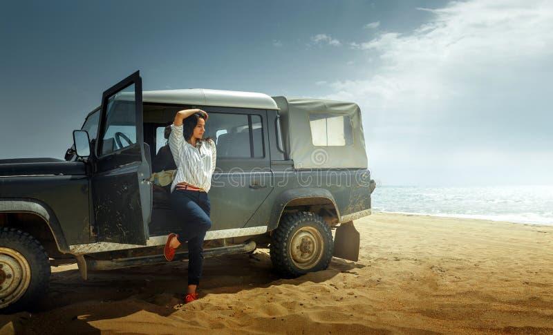 Attraktiver junge Frauen-Reisender, der die Seeansicht, zurück lehnend auf einem Oldtimer SUV genießt stockfotografie