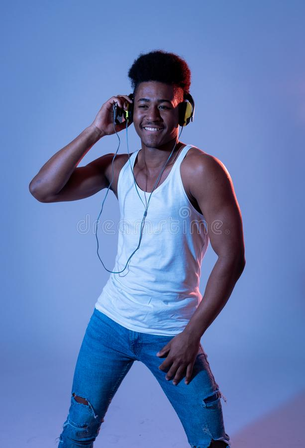 Attraktiver junger Afroamerikanermann mit den Kopfh?rern, die zur Musik auf Mobile im Discolicht tanzen und singen lizenzfreie stockfotografie