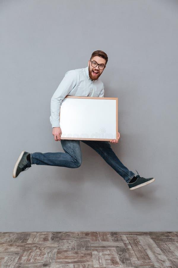 Attraktiver junger bärtiger Geschäftsmann, der das copyspace Brettspringen hält lizenzfreie stockbilder