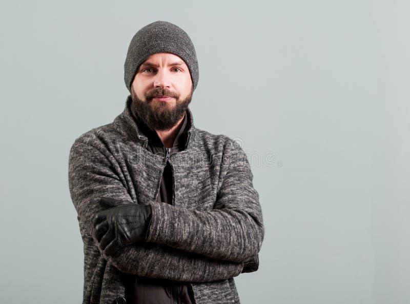 Attraktiver junger bärtiger Mann, der Arme gekreuzt und Lächeln hält stockfoto
