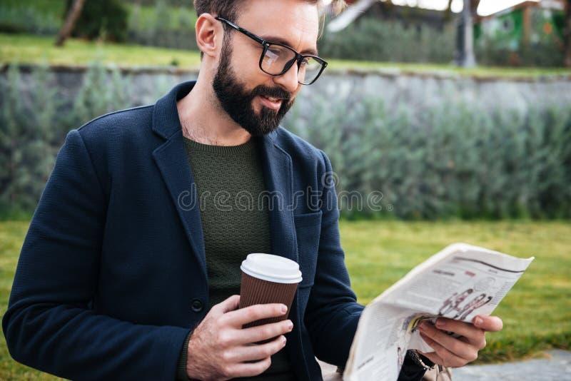 Attraktiver junger bärtiger Mann, der Zeitung sitzt draußen, lesend lizenzfreies stockfoto