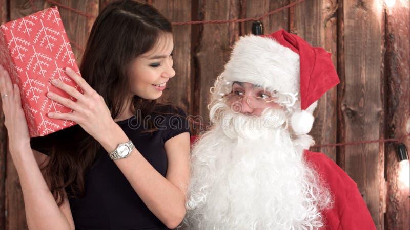 Attraktiver junger Brunette, der auf Santa Claus-` Schoss sitzt und ihr Geschenk überprüft stockfotos