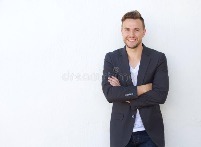 Attraktiver junger Geschäftsmann, der gegen weiße Wand lächelt lizenzfreie stockbilder