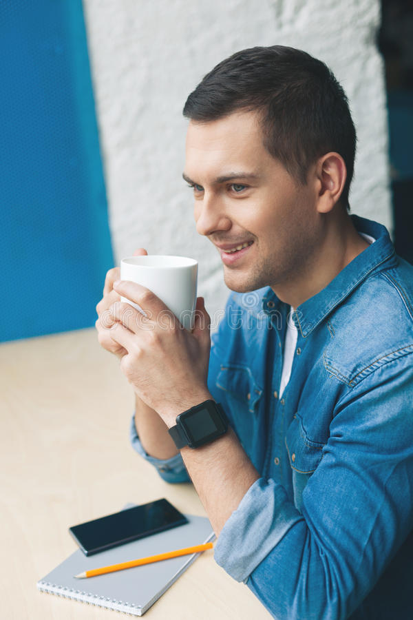 Attraktiver junger Kerl trinkt Heißgetränk stockfotos