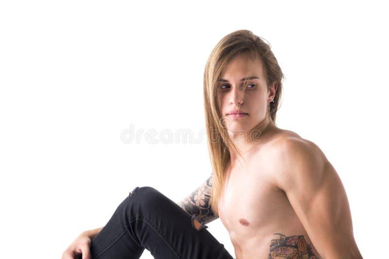 Attraktiver junger langhaariger Mann hemdlos, Sitzen, hinten schauend lizenzfreies stockfoto