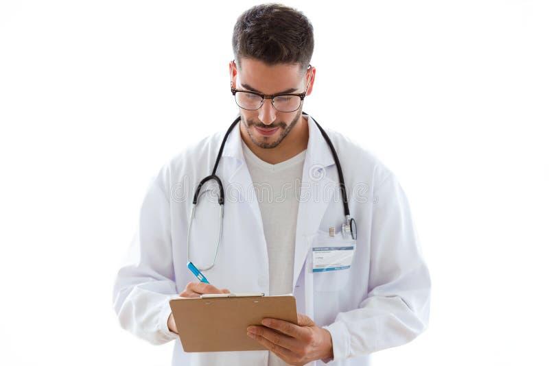 Attraktiver junger männlicher Doktor mit Stethoskop über dem Hals, der Kenntnisse im Klemmbrett lokalisiert auf weißem Hintergrun stockbilder