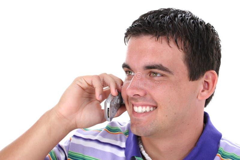 Attraktiver junger Mann auf Mobiltelefon mit Lächeln lizenzfreie stockfotos