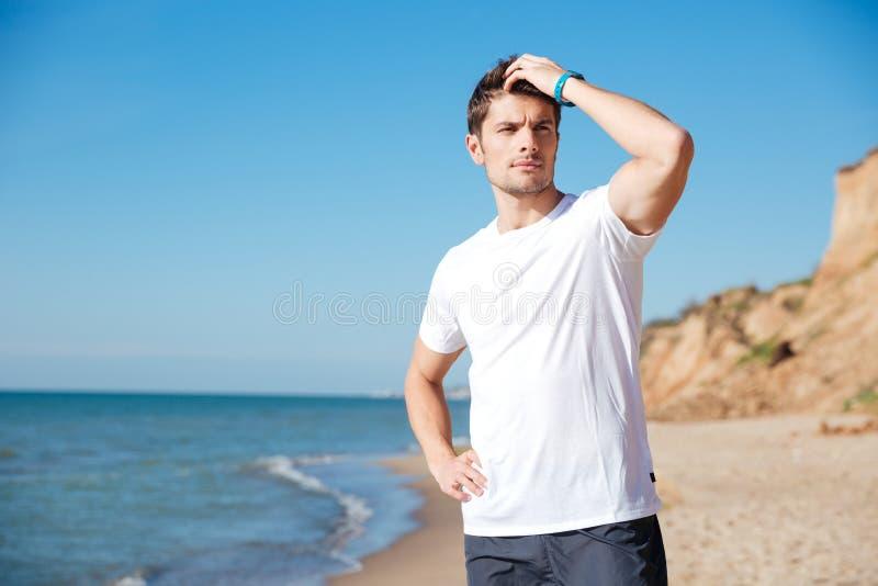 Attraktiver junger Mann, der auf dem Strand steht und denkt stockfotografie