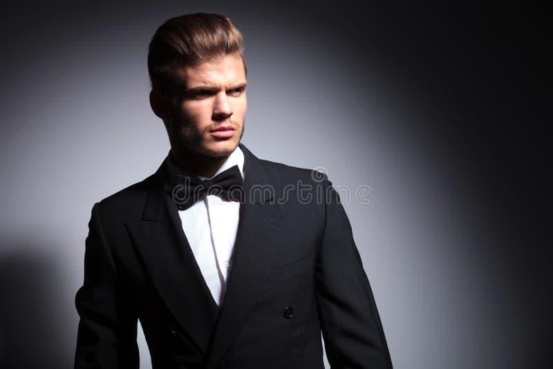 Attraktiver junger Mann, der eleganten schwarzen Anzug und Fliege trägt stockfotografie