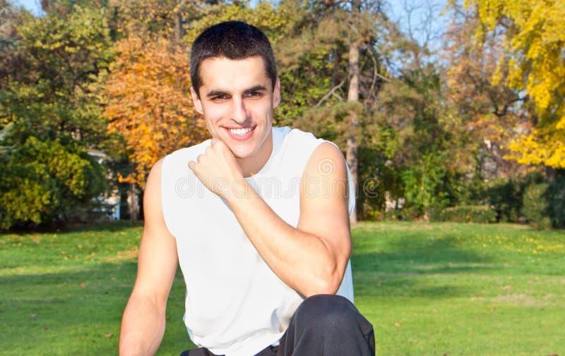 Attraktiver junger Mann, der im Park stillsteht stockbild