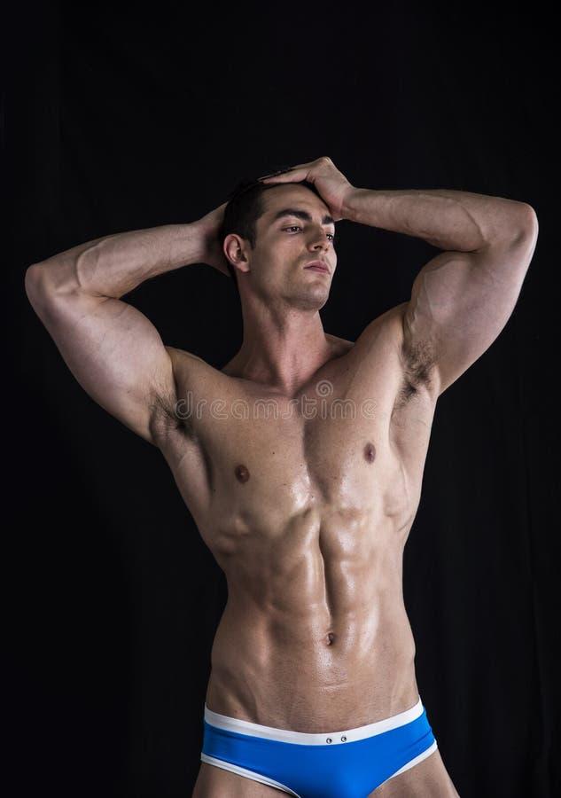 Attraktiver junger Mann, der mit muskulösem zerrissenem Körper steht lizenzfreie stockfotos