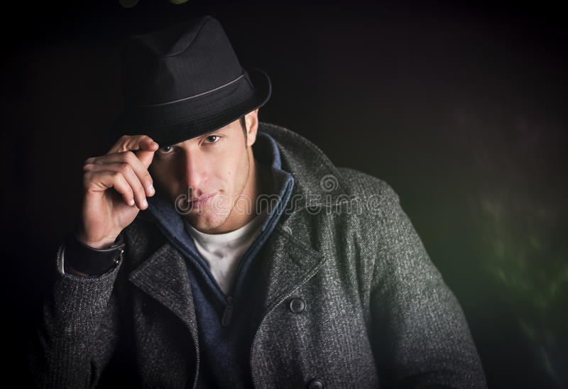 Attraktiver junger Mann an der Nacht, an tragendem Wintermantel und am Fedorahut stockbilder