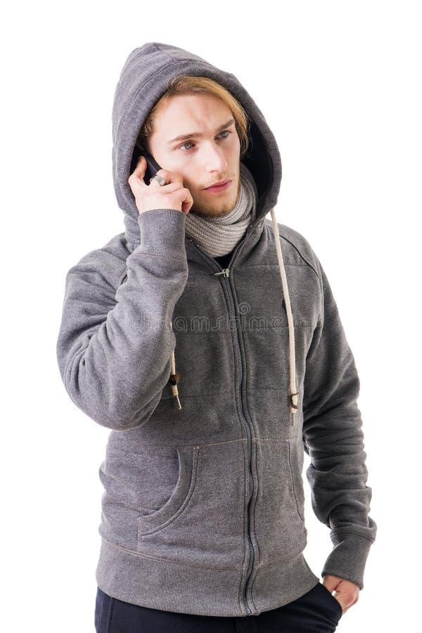 Attraktiver junger Mann, der um das Mobiltelefon, Textnachricht sendend ersucht lizenzfreie stockbilder
