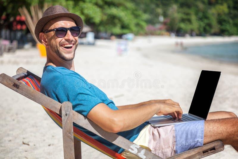 Attraktiver junger Mann mit dem Laptop, der an dem Strand arbeitet Freiheit, lizenzfreies stockbild