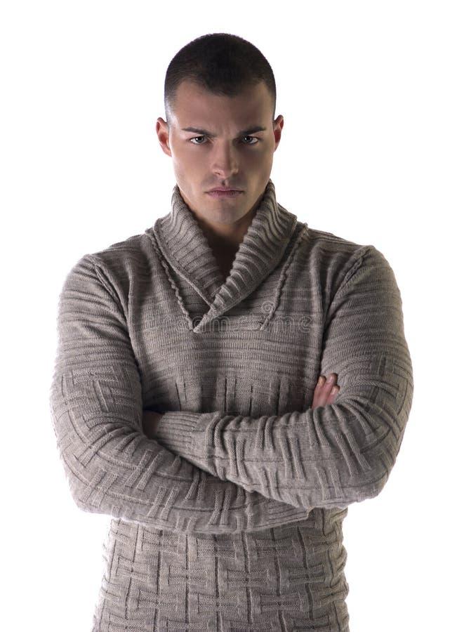 Attraktiver junger Mann mit strengem, schwerem Ausdruck, Arme kreuzte auf Kasten lizenzfreie stockfotos