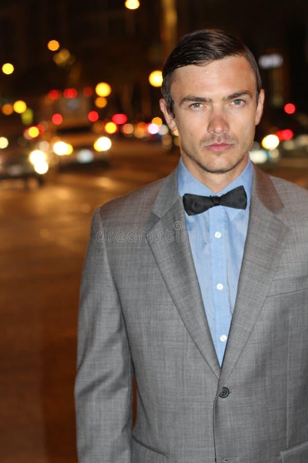 Attraktiver junger Mann nachts mit Stadt beleuchtet hinter ihm, tragender eleganter Anzugsjacke und Fliege stockfotos