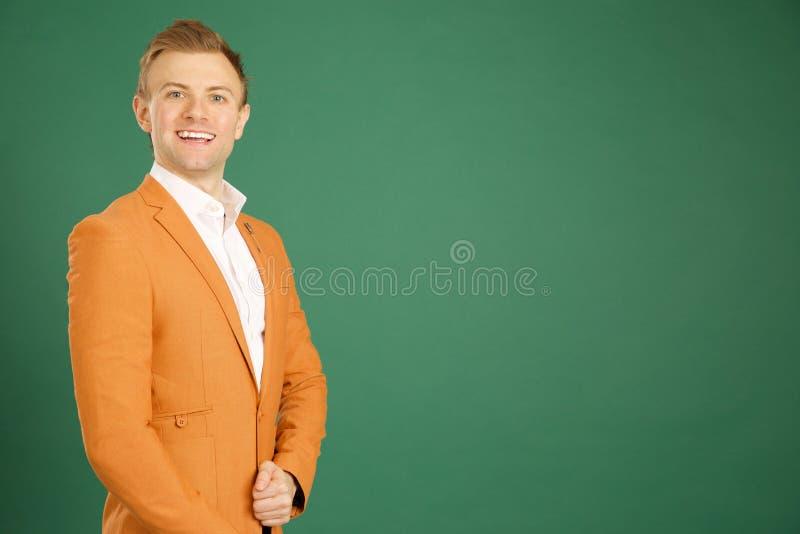 Attraktiver kaukasischer erwachsener Mann, der orange Jacke trägt stockbild