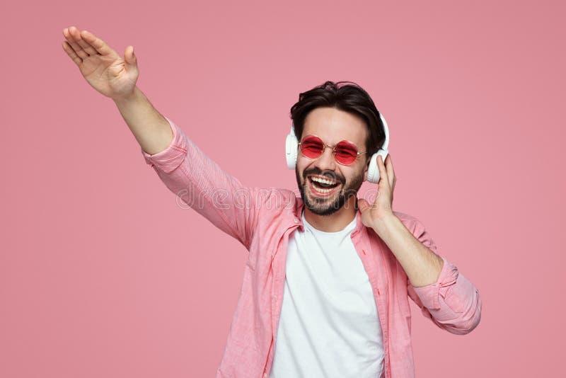 Attraktiver kaukasischer Hippie im rosa Hemd, das Spaß beim Hören Musik unter Verwendung der drahtlosen Kopfhörer über rosa Hinte lizenzfreie stockbilder