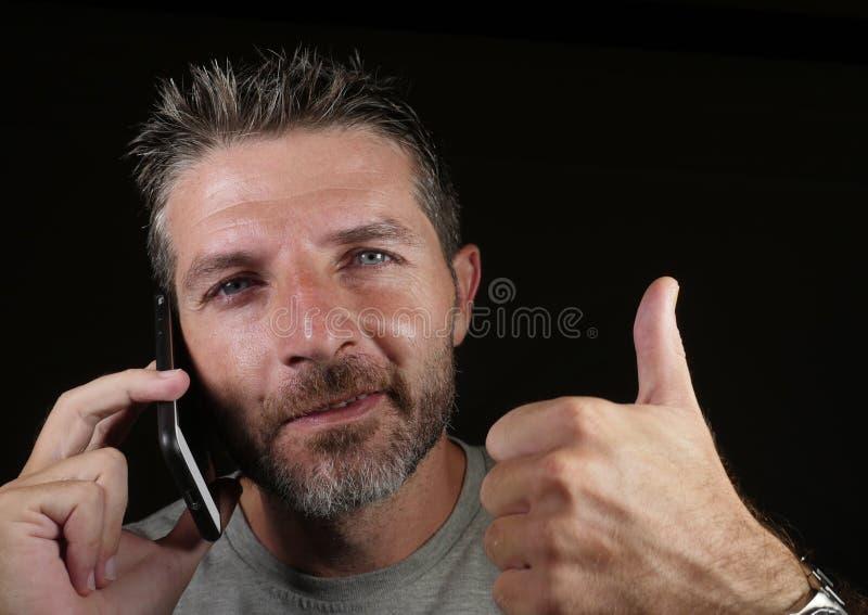 Attraktiver kaukasischer Mann, der am Handy hat das Geschäftsgespräch lokalisiert auf dem schwarzen Hintergrund aufgibt Daumen he lizenzfreie stockbilder