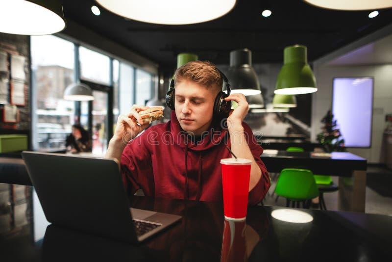 Attraktiver Kerl mit einem Burger in seiner Hand hört Musik in seinen Kopfhörern mit seinen geschlossenen Augen und benutzt einen lizenzfreie stockfotografie