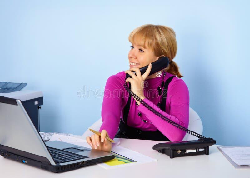 Attraktiver Mädchensekretär, der am Telefon spricht lizenzfreies stockbild
