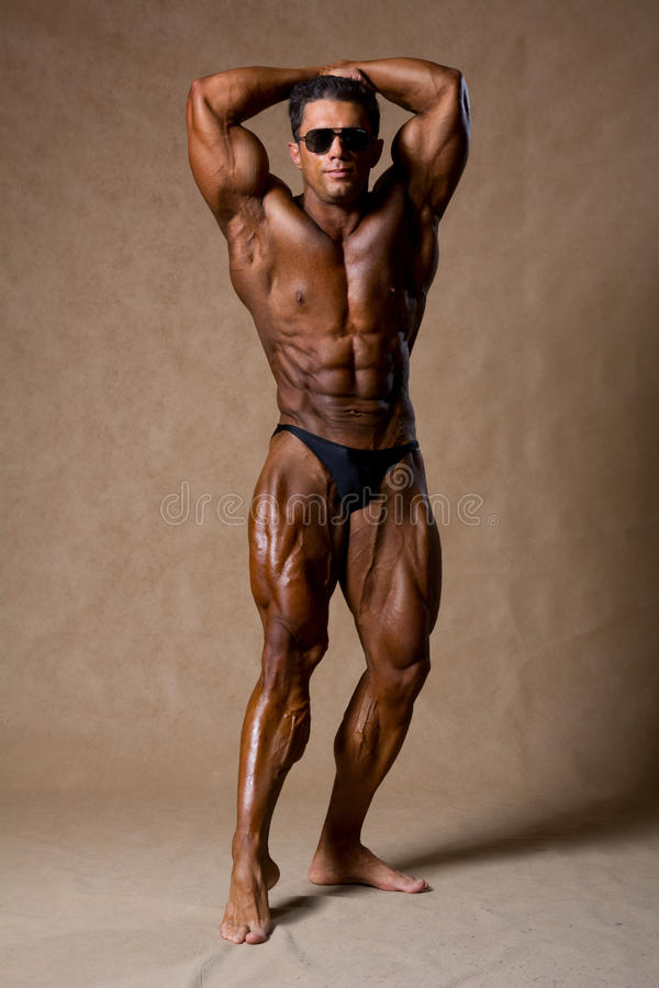Attraktiver männlicher Bodybuilder, Wettbewerbhaltung zeigend stockfotografie