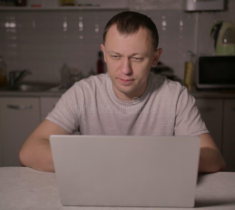 Attraktiver Mann, der am Abend in der Küche mit einem Laptop sitzt lizenzfreies stockbild