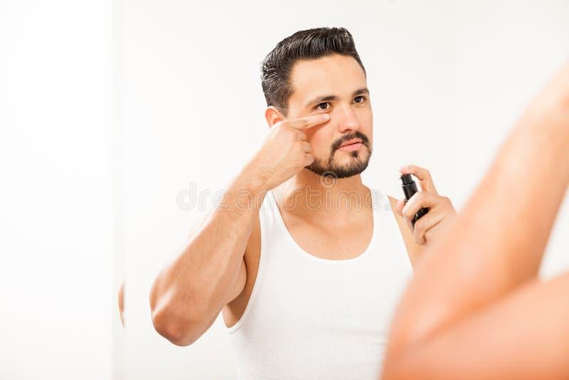 Attraktiver Mann, der Antialterncreme verwendet stockfotos