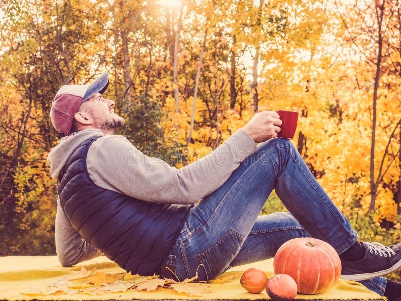 Attraktiver Mann, der auf der Terrasse im Hintergrund von gelben Bäumen sitzt lizenzfreie stockbilder