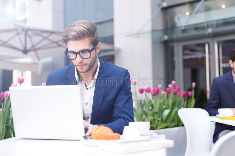 Attraktiver Mann, der an Computer im Café arbeitet stockfotos