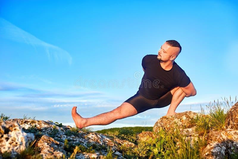 Attraktiver Mann, der Yoga auf dem Stein gegen hellen blauen Himmel mit Wolken tut stockbild