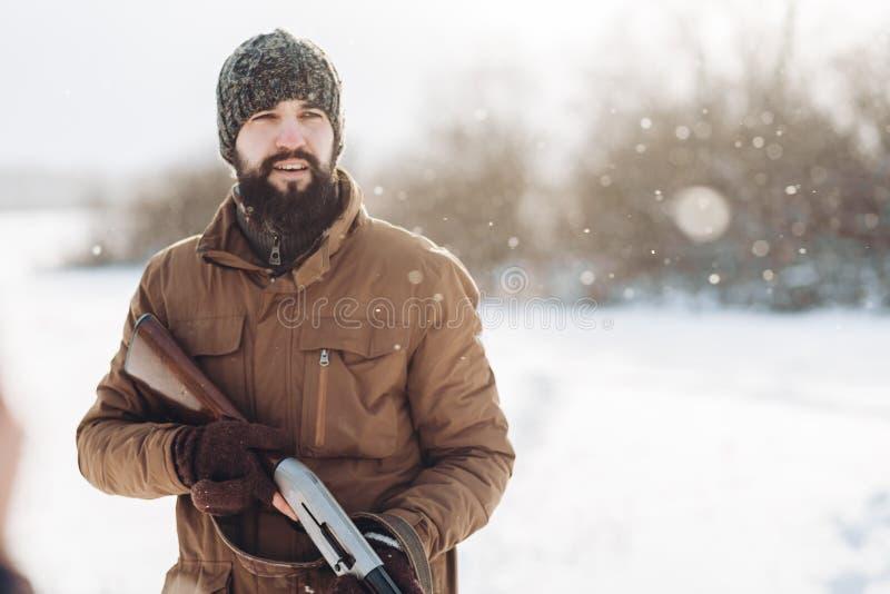 Attraktiver Mann in der zufälligen warmen Kleidung, die Spaß während der Jagd hat stockbilder