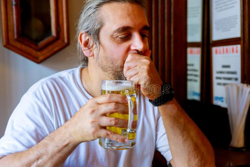 Attraktiver Mann in der zuf?lligen Kleidung trinkt Bier beim Sitzen am Barz?hler in der Kneipe stockfotografie