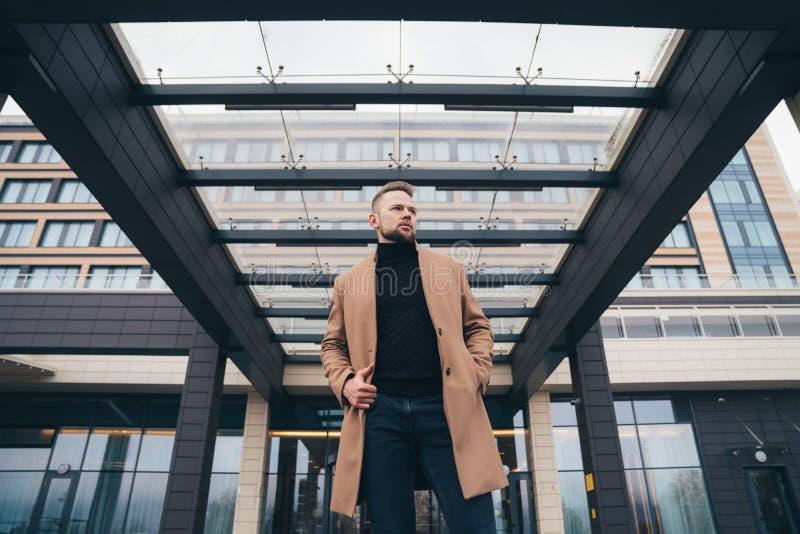 Attraktiver Mann im modischen braunen Mantel, der nahe Geschäftszentrum aufwirft r Konzept lizenzfreie stockfotografie